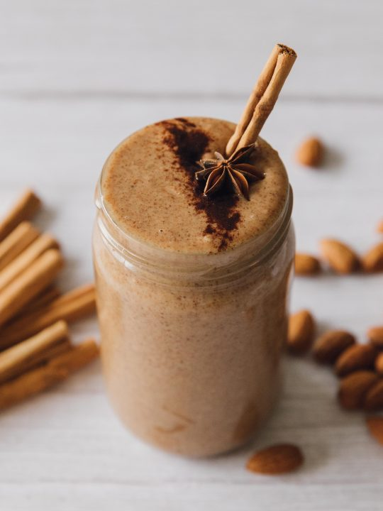 cinnamon almond butter in a jae=r with a cinnamon stick sticking out. more cinnamon sticks and almonds are in the background