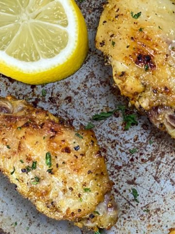 top close up of lemon pepper wins made in the air fryer, on a baking sheet with lemon slices