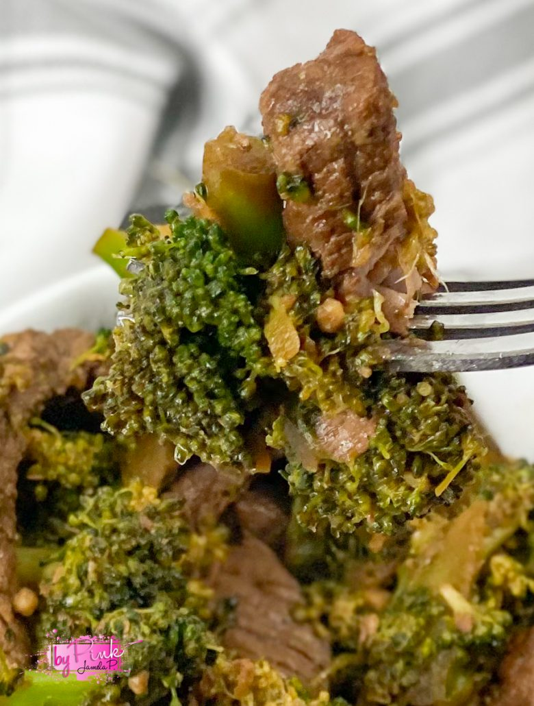beef and broccoli on a fork coming out of a white bowl