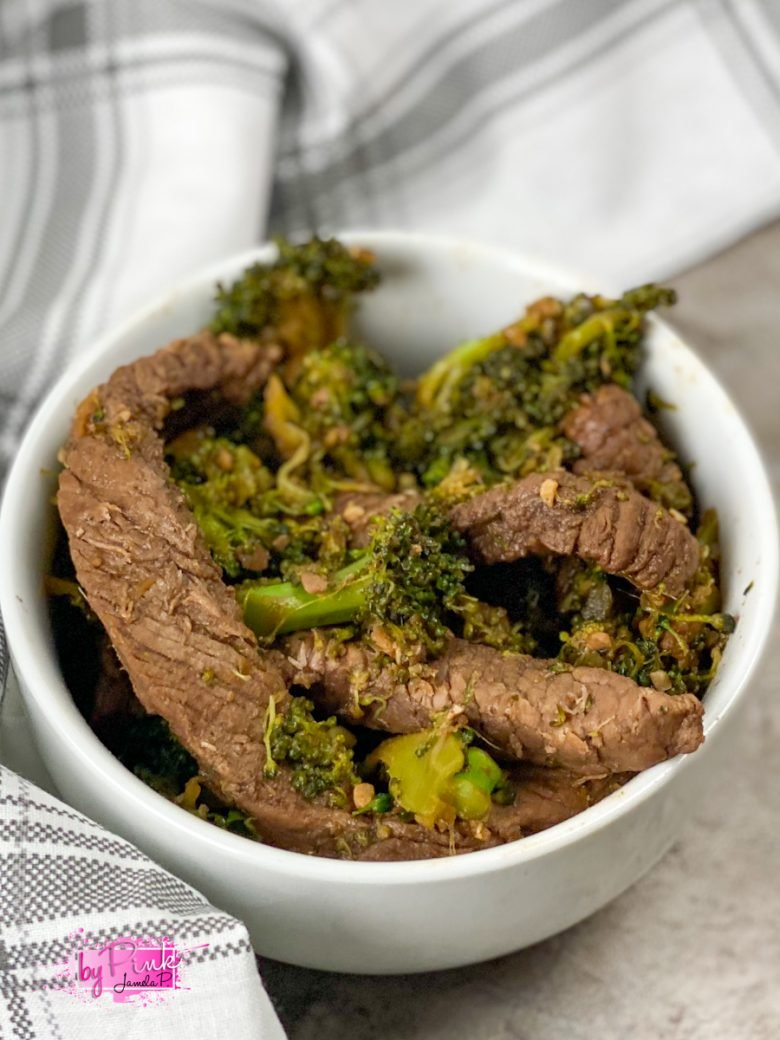 small white bowl with some keto beef and broccoli filling it up; striped napkin in the background