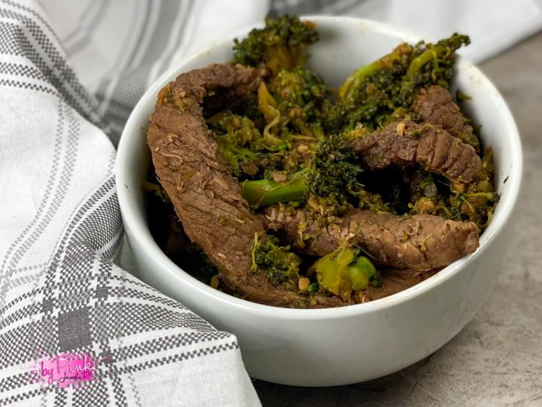 small white bowl filled with beef and broccoli that is low carb; small striped hand towel in the background