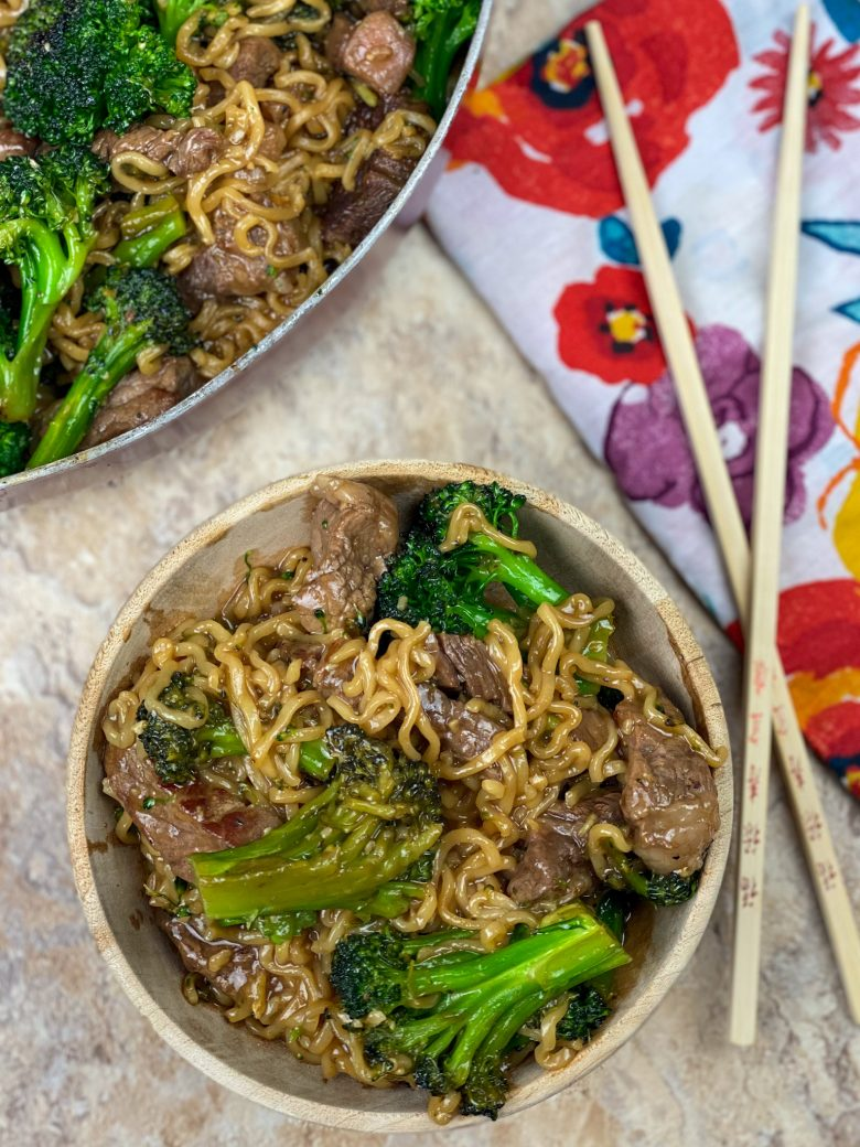 beef ramen stir fry with broccoli florets in bowl; chopsticks next to bowl of food