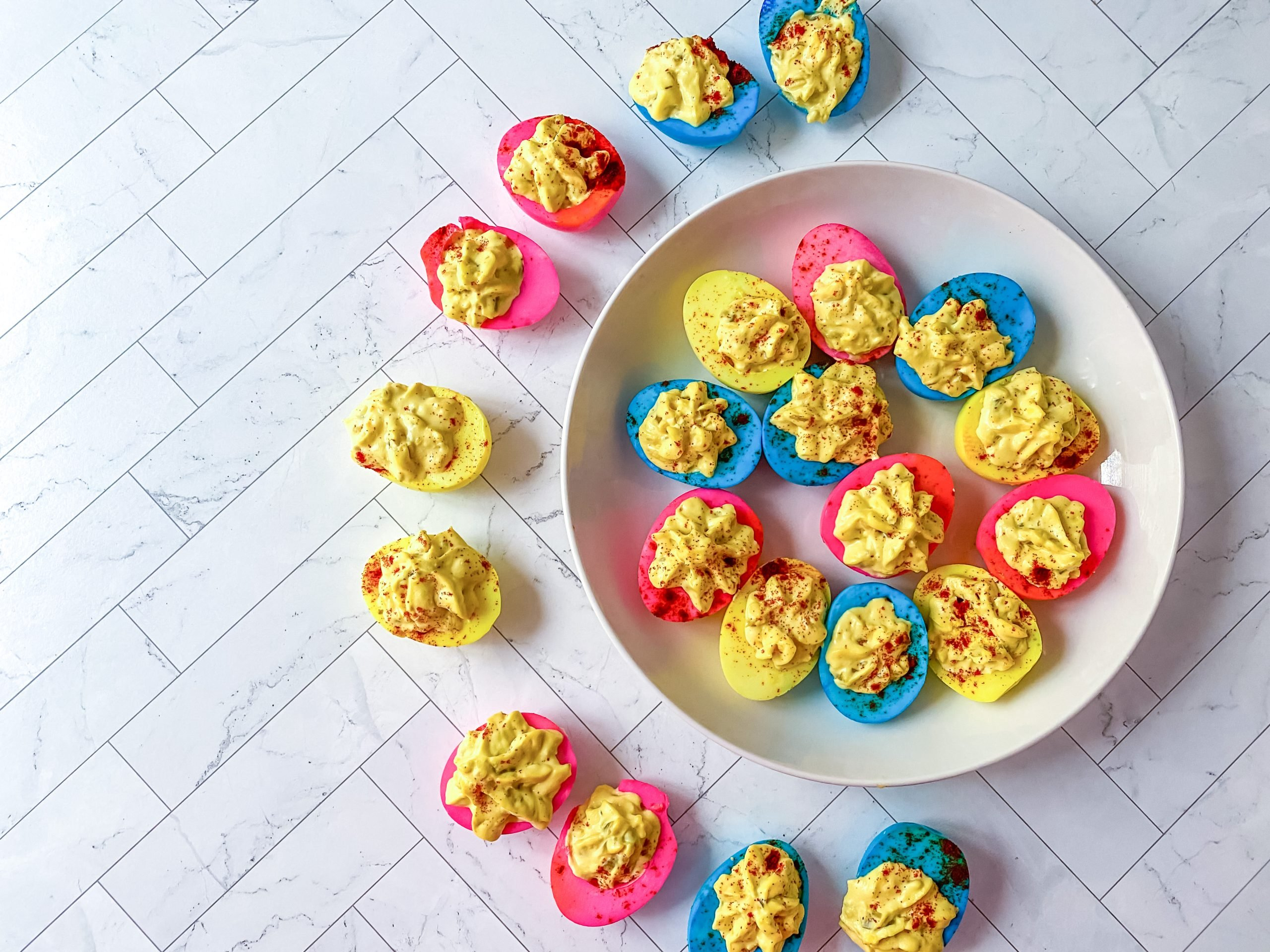 plate of multi colored deviled eggs that are blue, pink, and yellow.; deviled eggs surrounding half of the plate as well, filled with egg yolk mixture
