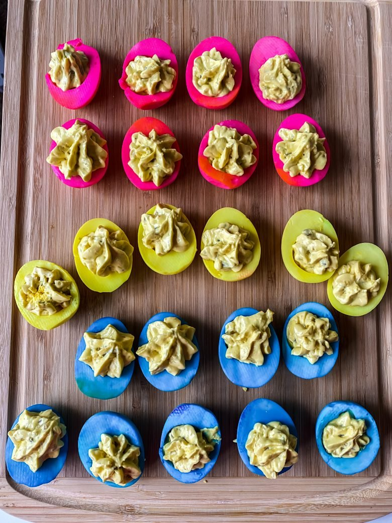 rows of deviled eggs that are pink, yellow, and blue on serving plate