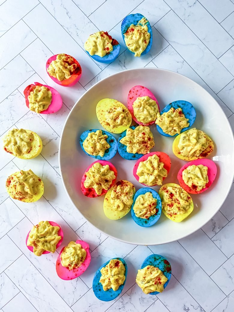 plate of deviled eggs that are blue, pink, and yellow.; deviled eggs surrounding half of the plate as well, filled with egg yolk mixture