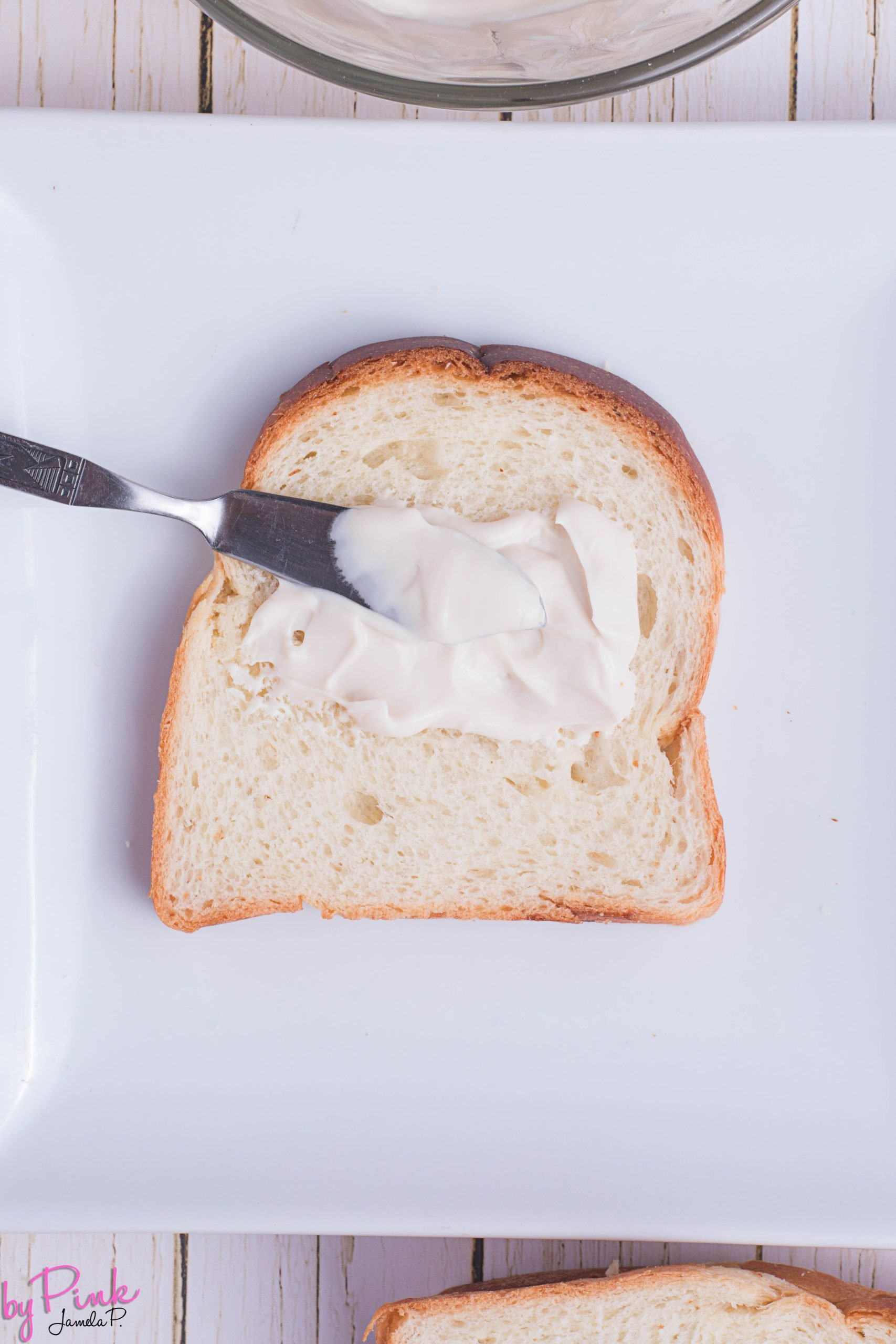 spreading cream cheese on thick bread