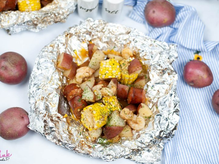 shrimp boil foil pack surrounded by potatoes